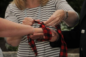 showing tartan ribbon being tied around couples hands during wedding