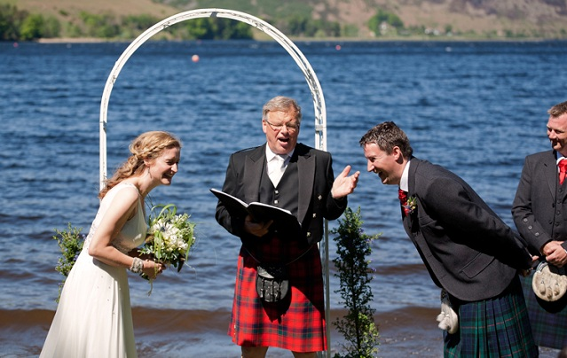 Wedding outdoors at St Mary's loch - photo of bride and groom laughing with celebrant during ceremony in front of loch