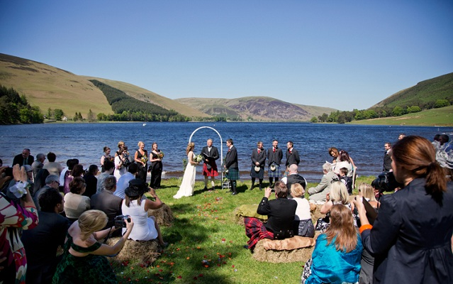 Wedding ceremony at St Mary's loch - photo of guests and couple during ceremony in front of loch and hills