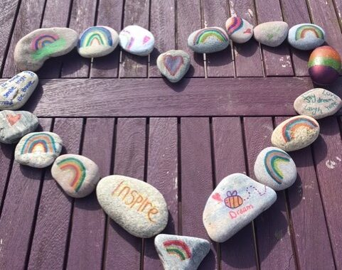 painted stones laid out in the shape of a heart